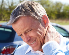 Side view of a male chiropractor examining mature man over white background