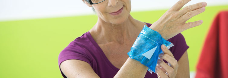 Woman placing an ice pack on her injured wrist