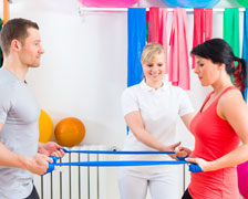 Physical therapists teaching a woman new exercises using elastic bands