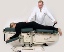 Chiropractor performing a back adjustment using the Flexion Distraction technique